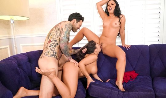 A tattooed man fucks his wife and her young girlfriend during a gangbang