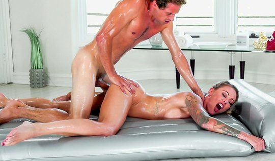 A young girl during a massage rubs her big milkings on a mans body